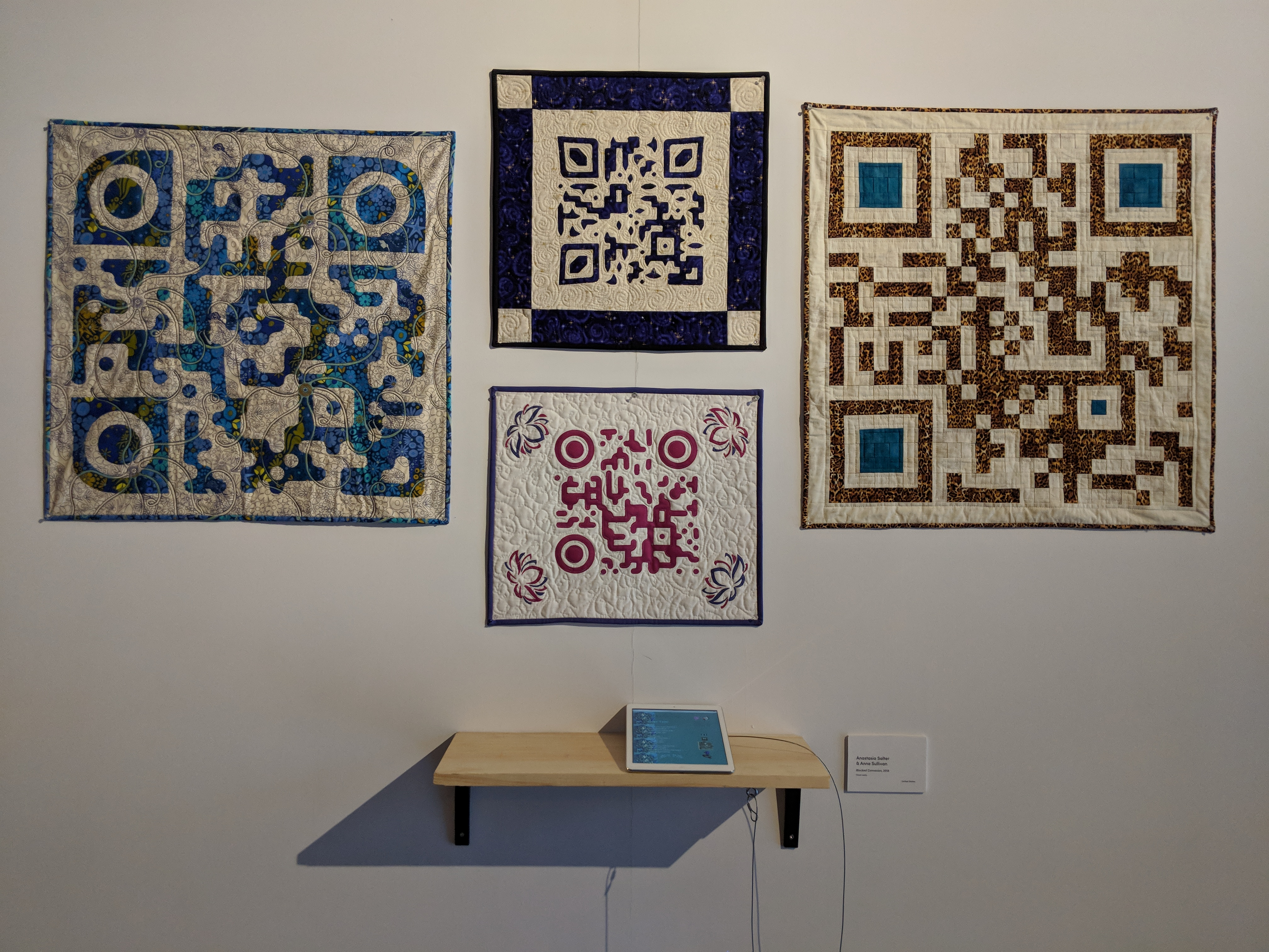 Four quilt blocks, two large and two small hang on a white wall. All four depict QR codes. The two large blocks are hung on either side of the smaller blocks, which are hung vertically with one above the other. Clockwise, starting at 12, the blocks appear as follows: 12 o'clock: a mid-sized border of purple fabric, except for off-white squares in each corner; The QR code is in the center, also in purple, on an off-white background. 3 o'clock (large): an off-white background, the QR code is mostly of brown fabric with three teal squares in the corners. 6 o'clock: a thin purple border around a swuare of white. Each corner has a pink design. In the center, the QR code is a darker pink. 9 o'clock (large); the background is a lightly patterned off-white fabric with a thin blue border; The QR code is made of mottled blue and brown fabric, likely a batik of some sort. Below the quilt squares, a blonde wood floating shelf hangs on the wall. A small white tablet is placed on the shelf.